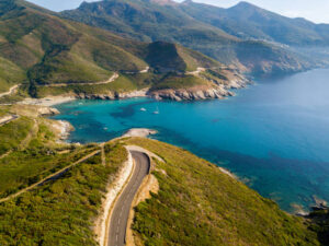 Aerial view of the coast of Corsica, winding roads and coves with crystalline sea. Cap Corse Peninsula, Corsica. Coastline. Anse d'Aliso. Gulf of Aliso. France